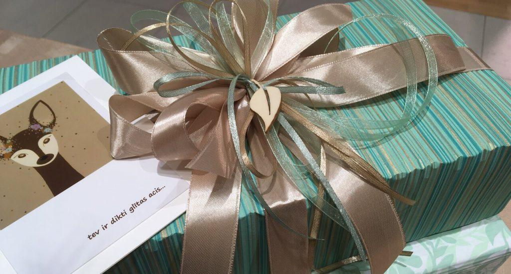 Dāvana ar pušķi un apsveikuma kartīte