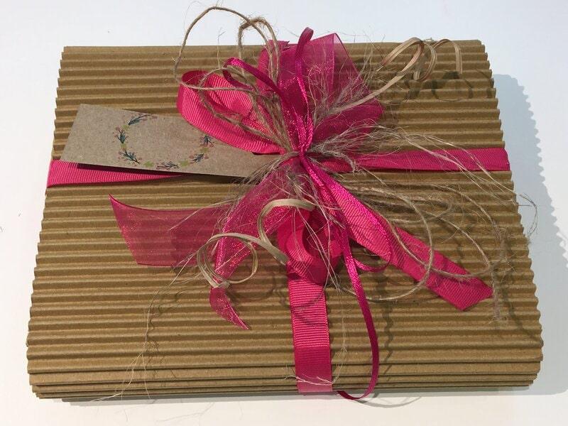 Gofrētā kartona dāvanu kastē iesaiņota dāvana ar vārda zīmīti