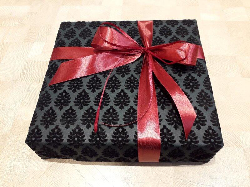 Dāvanu iesaiņošana melnā papīrā ar sarkanu lenti