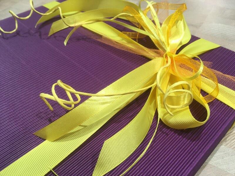 Dāvanu iesaiņošana - plakana violeta dāvanu kaste ar koši dzeltenu banti