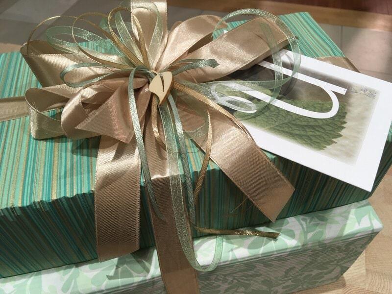 Dāvanu iesaiņošana - dāvana ar pušķi un apsveikuma kartīti