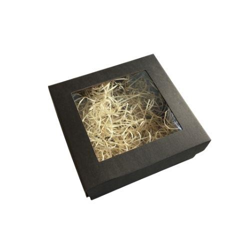 Melna kartona kaste ar caurspīdīgu lodziņu un koka skaidu pildījumu