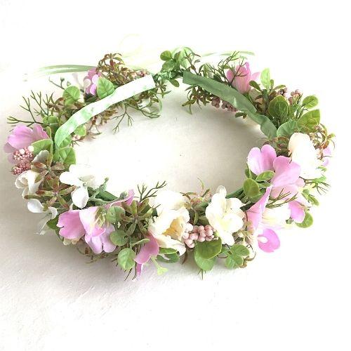 Rozā un baltu mākslīgo ziedu vainadziņš